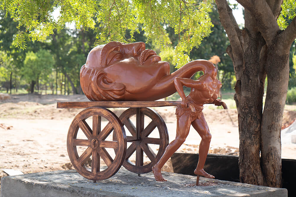 wooden carving of a man pulling a hand cart